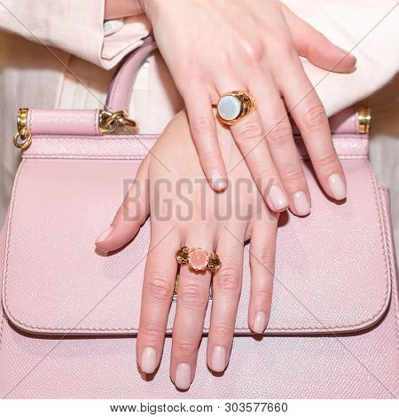 Woman Hands With Manicure And Luxury Jewelry Rings. Close Up Of Trendy Leather Pink Bag With Female