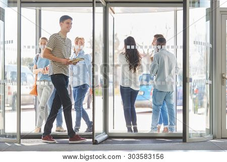 Young students in revolving door at university entrance