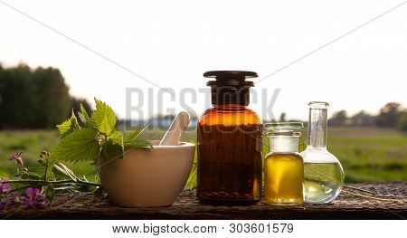 Alternative Medicine - Herbs And Oil. Mortar With Medicine Cross, Fresh Herbs And Essential Oil Bott