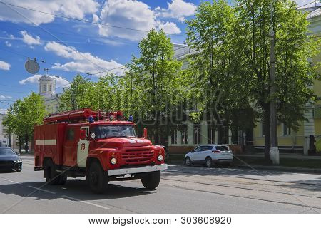 A Firetruck Speeding Down A Street To A Call.
