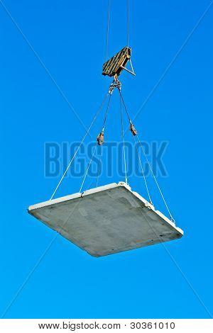 Elevating crane lifting a concrete plate
