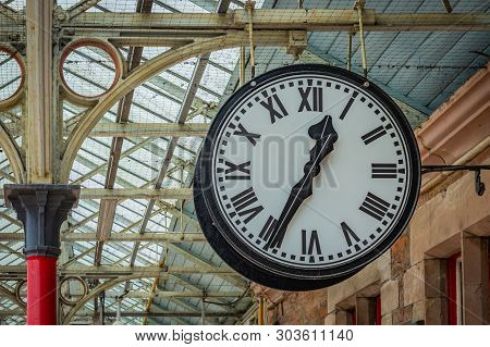 Big White Clock With Black Numbers In The Train Station Hall