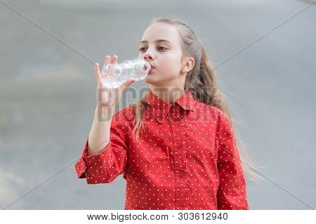 Water Is Life. Thirsty Child Drinking Fresh Water From Plastic Bottle. Little Girl Having A Drink Fr