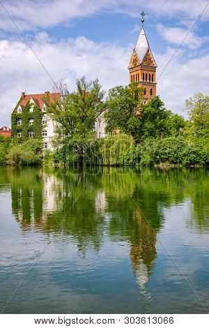 Landshut townscape with Christ Church (Christuskirche) reflecting in Isar river on a bright spring day, Bavaria, Germany, Europe poster