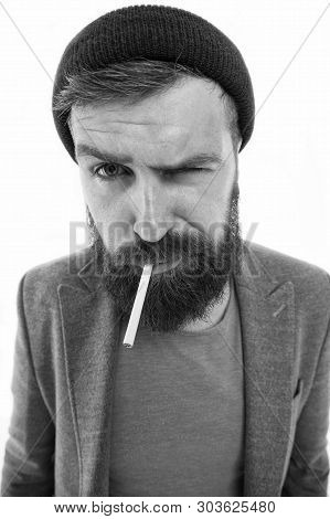 Brutal habits and lifestyle of tramp. Hipster brutal bearded tobacco smoker. Man brutal bearded hipster dressed as vagabond smoking cigarette. Brutal unshaven guy smoking isolated white background. poster