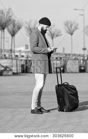 poster of Let travel begin. Traveler with suitcase waiting transportation to airport railway station. Ready to travel. Carry travel bag. Business trip. Man bearded hipster travel with big luggage bag on wheels.