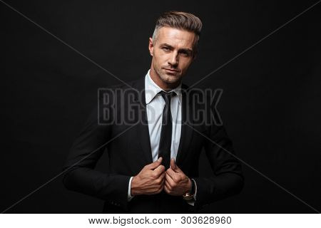 Portrait of confident businessman dressed in formal suit touching his jacket and looking at camera isolated over black wall