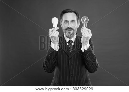 Man Bearded Consultant Formal Suit Hold Light Bulb On Red Background. Symbol Of Idea Progress And In