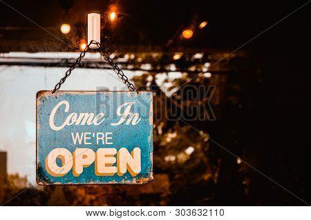 Come In We're Open Sign On Door Of Coffee  Shop.
