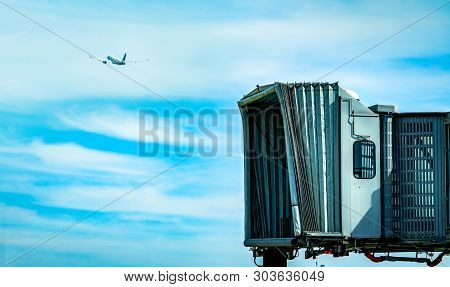 Jet Bridge After Commercial Airline Take Off At The Airport And The Plane Flying In The Blue Sky And