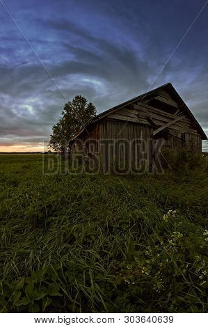 The Clouds Create A Round Formation Over An Old Barn House On A Late Summer Night At The Northern Fi