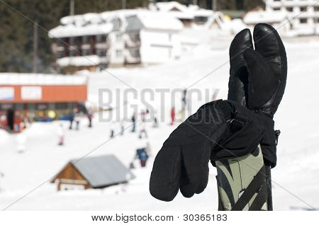 Ski Gloves And Sticks. Winter Tourists On The Background