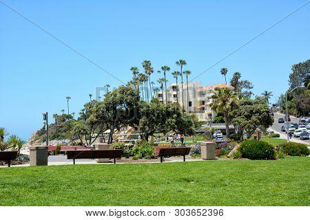 LAGUNA BEACH, CALIFORNIA - MAY 28, 2019: Main Beach Park in the popular beachtown looking up PCH towards the Inn at Laguna Beach.