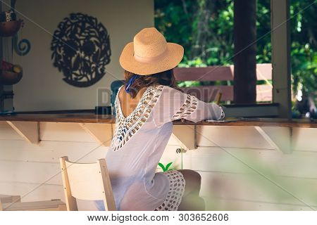 Attractive Woman Relaxing At Beach Bar In Vacation. Woman Relaxing In Bar In Vacation. Vacation Life