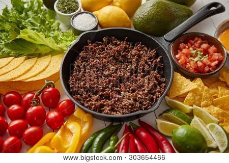 Chili con carne in frying pan on white wooden table. Ingredients for making Chili con carne.Top view. Chili with meat, nachos, tacos, limes, avocado, hot pepper. Mexican Texas traditional dish