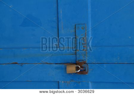 Old blue door with rusty lock attached poster