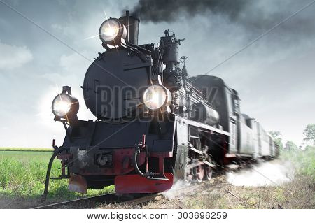 Old Passenger Train Running On Tracks Through The Forest. Retro Locomotive With A Steam Engine, Smok