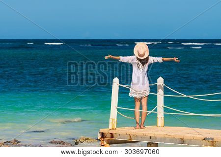 Beautiful Woman On Docks With Hands Outstretched. Vacations Lifestyle. Woman Relaxing On The Beach.