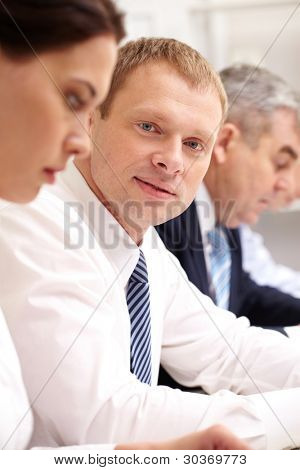 Handsome man taking part in business meeting and smiling at camera