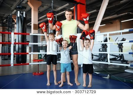Little children with trainer in boxing ring