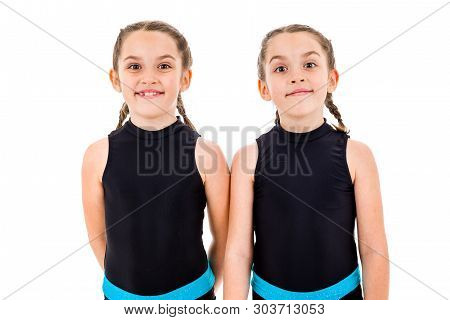 Identical twin girls practice and doing rhythmic gymnastics, white background. Young sister girls are dancing and having fun performing rhythmic gymnastics exercises. Isolated on white background. poster