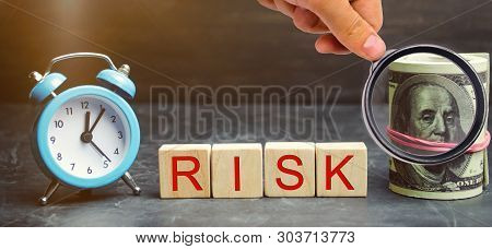 Money, Clock And Wooden Blocks With The Word Risk. The Concept Of Financial Risk. Justified Risks. I