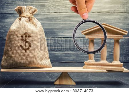 A miniature bank and money on the scales. The concept of successful investment in the bank. Credit / Loan / Deposit.The concept of dividend payments. Banking system, investment in the economy poster