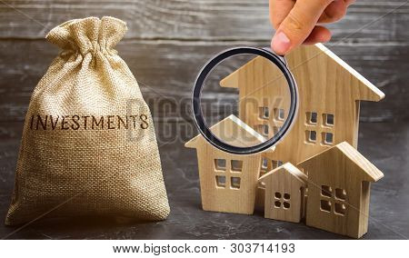 Money Bag With The Word Investments And Wooden Houses. The Concept Of Attracting Investment In Real