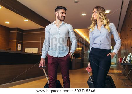 Young Couple Near Reception Desk In Hotel. Young Couple Leaving Hotel
