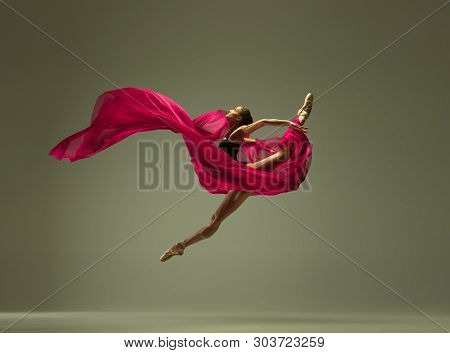 Graceful Ballet Dancer Or Classic Ballerina Dancing Isolated On Grey Studio Background. Woman With T