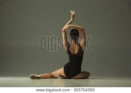 Graceful Ballet Dancer Or Classic Ballerina Dancing Isolated On Grey Studio Background. Showing Flex