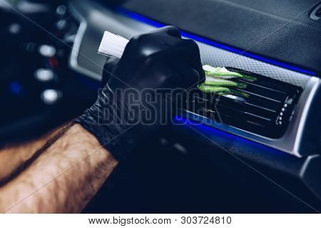 Man Worker In Car Wash Cleaning Car Air Vent. Car Detailing