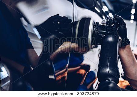 Man Worker In Car Wash Polishing Car With Electric Polisher