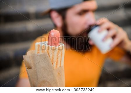 What A Sausage. Hipster Drinking Coffee With Hotdog Snack On Stairs Outdoor. Caucasian Guy Enjoying