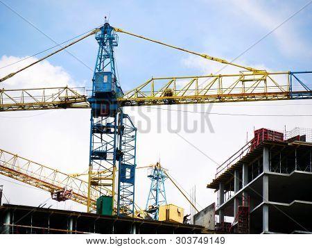 Construction Crane Near The Building Under Construction. Close Up Of A Construction Crane. Self-erec