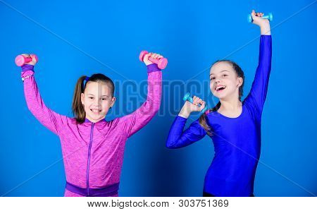 Easy exercises with dumbbell. Sporty upbringing. On way to stronger body. Girls exercising with dumbbells. Beginner dumbbells exercises. Children hold dumbbells blue background. Sport for teens poster