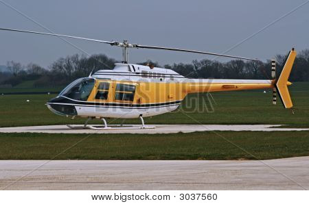 Grounded White And Yellow Helicopter At Airport