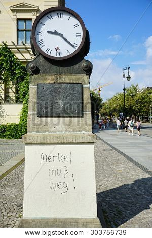 Political Commentary About Angela Merkel Is Written On A Monument With A Clock, Conceptually Indicat