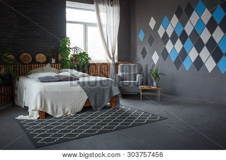Stylish Loft Cozy Living Room With Double Bed, Carpet, Armchair, Green Plants And Geometrical Patter