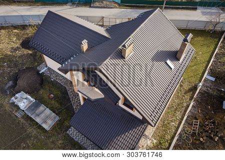 Aerial Top View Of Building Steep Shingle Roof, Brick Chimneys And Small Attic Window On House Top W