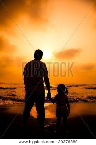 a silhueta do pai segurando a mão da menina na praia