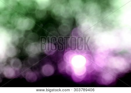 Purple And Green Haze Bokeh Sunset  Behind Trees Intentionally Blurred To Create An Abstract Effect.