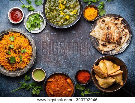 Overhead Of Indian Traditional Dishes And Appetizers: Chicken Curry, Pilaf, Naan Bread, Samosas, Pan