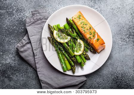Grilled Salmon Fillet With Green Asparagus And Seasonings On Plate, Gray Concrete Background. Health