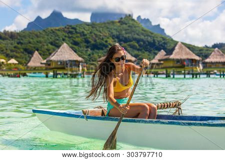 Outrigger Canoe - woman paddling in traditional French Polynesian Outrigger Canoe for recreation water sport competition. Bora Bora with Mount Otemanu and overwater bungalow resort hotel.