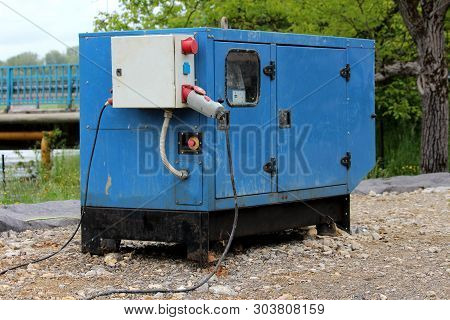 Heavy Enclosed Industrial Power Generator Located Next To River Providing Electrical Power To Large