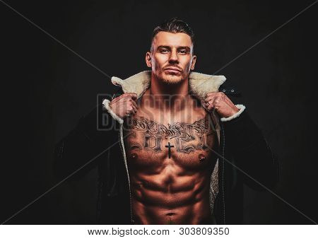 A Macho Stylish Man In Jeans Jacket With Naked Torso And Stylish Hair Over Dark Background.