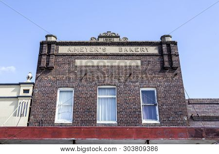 Glen Innes, Australia - April 12, 2019: Facade Of A 1921 Brick Commercial Building With Tall Parapet