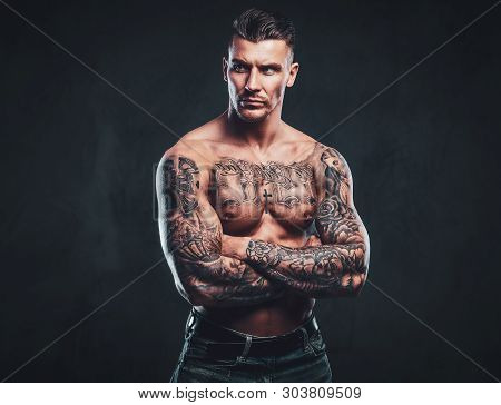 A Tattooed Muscular Shirtless Man With Stylish Hair Posing At The Camera Over Dark Background.