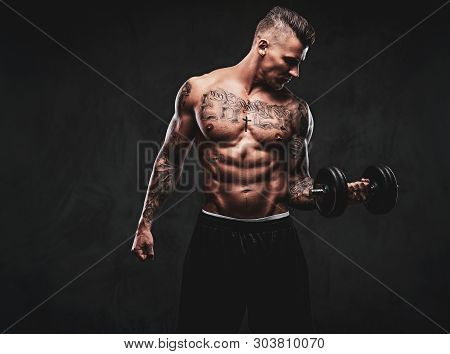 A Tattooed Muscular Man Doing Exercises With Dumbbells For Biceps On Dark Background.